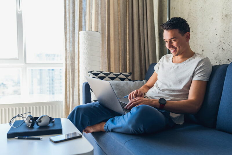 young attractive man sitting on sofa at home working on laptop online using internet 1